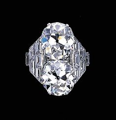 An impressive twin-stone diamond ring, by Cartier Set with two old mine-cut diamonds weighing 6.13 and 6.33 carats to the tiered baguette-cut diamond shoulders and plain hoop, circa 1935