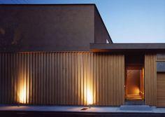 日本建築の様式美でもある直線を基調とした玄関。 日が暮れると点灯する壁面を照らす照明は質感と暖かさを演出します。