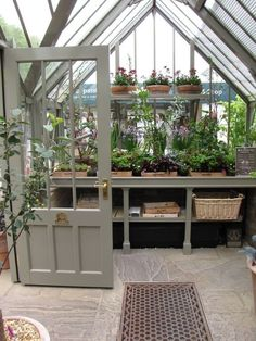 One day maybe I will have my own green house! INDOOR GARDEN :: Love love love this greenhouse! GOOD IDEA: Keep plants together on wooden trays labeled with the types of plants. | #greenhouse #greige #houseplants #greenhouseeffect