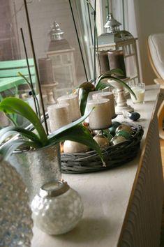 Fensterrahmen befüllt mit Kerzen, Leuchten und Orchideen