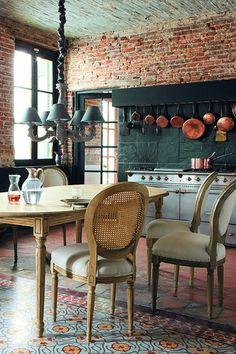 Exposed Brick - hanging copper pots - huge cooker - black slate splashback