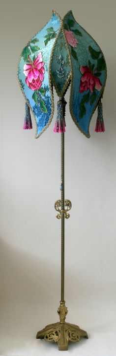 Gold 1920s vintage floor lamp holds a Chinese Peony shade in vibrant green and blue tones and overlaid with wonderful vintage fuchsia peony Chinese appliques. The side panels have antique ornate blue and metallic chinoiserie appliques. Four hand beaded tassels adorn the corner and a jeweled pull chain completes the look