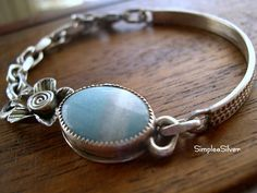 This beautiful, robins egg blue, amazonite has been set in a fine and sterling silver bezel. I have soldered a fine silver flower to the bezel. Connected to the bezel is curved length of substantial,patterned wire in sterling silver and connecting to the fine silver flower is a length