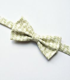 DESCRIPTION: This floral mens bow tie has been handmade using a white and olive green vine print cotton. FABRIC: Cotton.  --------------------------------------------------------------------------------------------  DETAILS: • This bow tie is pre-tied • Attached to an adjustable strap fitting approx 15inch - 19inch neck size • Neatly packaged in a smart box with ribbon and tag attached • Lovingly handmade in the UK • Postage - UK delivery is sent first class with proof of postage, all other…