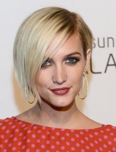 Dark roots blonde asymmetrical bob haircut with side part and long wispy side swept bang hairstyle