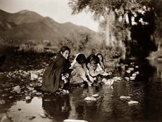 Photo of Taos Indian Children. It was made in 1905 by Edward S. Curtis.    The illustration documents Four Taos children squating on rocks at the edge of a stream, with mountains in background.    We have compiled this collection of artwork mainly to serve as a vital educational resource. Contact curator@old-picture.com.    Image ID# 0A29A291