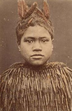 A young male wearing a flax cape, kotikoti. Hand-coloured, c 1890's. The boy wears kaka (parrot) feather decoration.