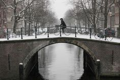 A cyclist rides over a bridge on one of the canals in the center of Amsterdam,