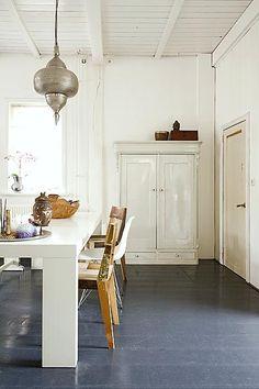 Eenheid in kleur creëert rust: de antieke kast werd in dezelfde kleur als de muur geschilderd en ook de tafel is een wit exemplaar.