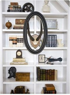 8 tips for giving your bookcase a decorative look, home decor, painted furniture, shelving ideas, A great mix of books with decorative pieces This bookcase definitely uses the back to front approach by hanging artwork on the frame via HGTV