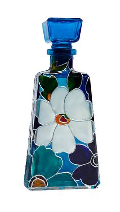 Hand Painted Glass Bottle This gorgeous bottle is a decanter with glass stopper and it is hand painted in a blue/white floral design. This is the perfect piece to light up your living room, bedroom, or kitchen! This work of art should be set in a place well exposed to the light so its beauty can radiate and be adored. This beautiful piece makes the perfect, unique present for any occasion! MEASUREMENTS: Height: 8 in ( only bottle) , with the stopper 9 1/2 in Base measureme...