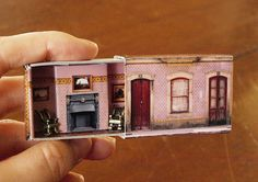 A regular matchbox is given a makeover to become a cute little house that can fit in your hand. Photographs cover the box and metal furniture