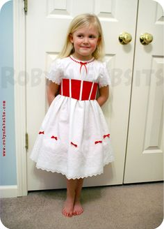 we can find white dresses for the girls and add on the red (fake corset) material. Accent with bows.