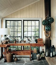 Use a vintage workman's table as a casual bar for an entryway to a woodsy summer cabin | domino.com