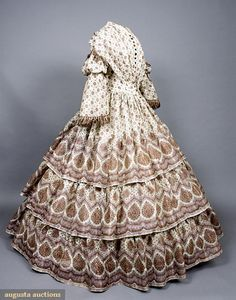 Printed Wool Gauze Day Dress, 1850's. Sheer wool printed with purple and brown border design, trimmed with silk fringe, fitted bodice coming to point at center front with extra fabric pleated in at waist, full tiered sleeves with epaulets, three tiered skirt, pocket under one tier, front hook opening with black button trim.