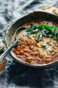 Instant Pot Minestrone Soup! Thick + chunky with veggies, garlic, beans, pesto, tomato sauce. Topped with Parm and served with bread. Easily made vegan.