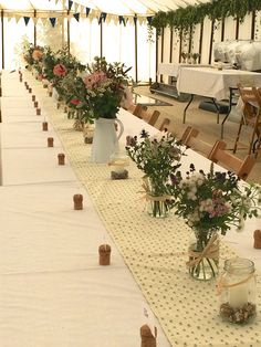 Flowers in jugs and jam jars on trestle table