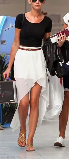 White high low skirt, black crop top, and gold sandals.