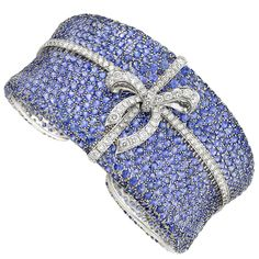 White Gold, Sapphire and Diamond Cuff Bangle Bracelet. 18 kt., the wide tapered bangle encrusted with 40.55 carats of round sapphires, centering a continuous line of round diamonds, accented by a diamond-set ribbon and bow, altogether ~ 3.55 cts.