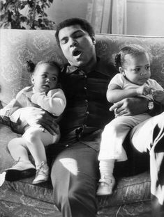 December Muhammad Ali yawns while babysitting two of his daughters by wife Veronica Porche, 9 month old Laila (left) and 2 year old Hana (right). They are at Grosvenor House in London. (Photo by Frank Tewkesbury/Evening Standard/Getty Images) Mohamed Ali, Muhammad Ali Boxing, Float Like A Butterfly, Boxing Champions, Hometown Heroes, Robert Burns, Ali Quotes, Black Families, New Politics
