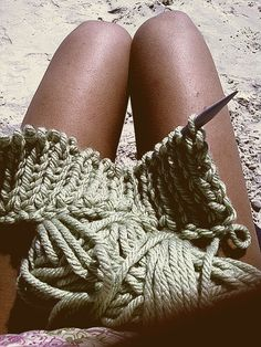 Knitney Spears kniting on the beach.
