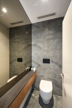 Stone clad walls and floor, mixed with smokey mirror create a feeling of luxury and calm in this powder room, adjacent to the master ensuite which uses the same materials. Interior Designers Melbourne, Powder Room, Building Design, Walls, House Design, Flooring, Contemporary, Mirror, Stone