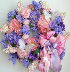 """The wreath is embellished with beautiful pink/lavender Peonies, lavender Roses, lavender Baby Breaths, pink/white Lilacs,and pink/lavender/purple Hydrangeas. The wreath is accented with two white Butterflies . I finish the wreath with a pink chevron and lavender Ribbon Bow.   The wreath measures from tip to tip at 24"""" (L) x 24"""" (W) x 7""""(D)."""