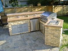 Outdoor Kitchen, This space is a renovation of an existing patio space. A new outdoor kitchen was created with a grill, refrigerator, sink and storage. The island is cast stone with cast countertops. The island has also been outfitted with lighting and outlets. Surrounding the island is a new paver patio., Bird's eye view of kitchen.   , Patios & Decks Design