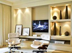 Estante feita com gesso em diferentes níveis + iluminação embutida, uma ótima ideia para resolver problemas com pilares na parede da tv. Projeto Débora Aguiar.