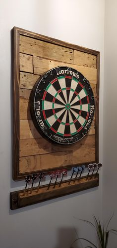 """Custom dartboard backing and dart holder I made. Just used cedar and old pallet wood. Pretty basic but looks nice. I hadent seen a dart holder out there like it though. I think the angle is a good idea. Stained with """"Dark Walnut"""" and """"Espresso"""" Dartboard Backing, Dartboard Surround, Dartboard Stand Diy, Dartboard Cabinet Plans, Dartboard Wall Protector, Dartboard Ideas, Game Room Bar, Game Room Decor, Woodworking"""