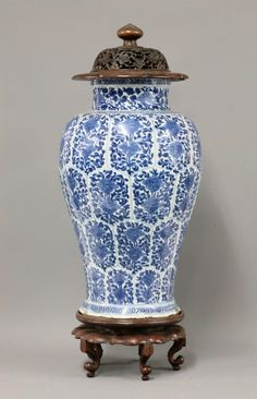 An attractive blue and white baluster Vase, Kangxi, lightly moulded with interlocking lotus panels and each painted within with two peony and lotus scrolls, wreath borders, minor chips, 42cm high