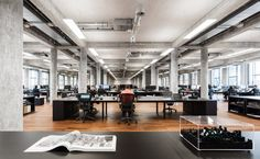 A large shared working area forms the core of this office, with banks of long desks forming three rows across the breadth of the building. Window on both side ensure the space is amply lit and offer views over the waterfront.