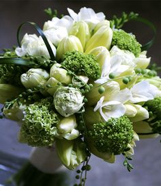 Bridal floral arrangement designed with French tulips, vivurnum, freesia green pearl necklace plant.