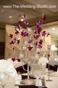 Silver tree branch, white votive candles, and purple leaves for this table setting. The Wedding Studio, Schaumburg