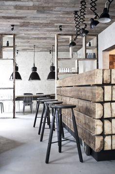 <p>Norm Arkitekters slanke barkrakker er typisk for den nye nordiske trenden – her i spennende kombinasjon med grovt tømmer som er brukt i bardisken. Tøffe, industrielle lamper i svart med bevegelige trekkspillarmer sørger for riktig belysning.</p>