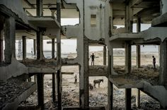 People look for concrete to salvage in a building in Gaza on August 3, 2015. (Tomas Munita for The New York Times)