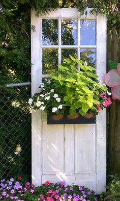 Create this garden spot with an old window door and an attached container of flowers!...old screen door also...