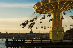 """Balanços no ar na atração Carrocel no parque de diversões Gröna Lund, na ilha de Djurgården, Estocolmo, Suécia. Gröna Lund, o mais antigo parque de diversões do país, tem sido chamado de """"Feira do Trono"""" de Estocolmo.  Fotografia: Benoît."""
