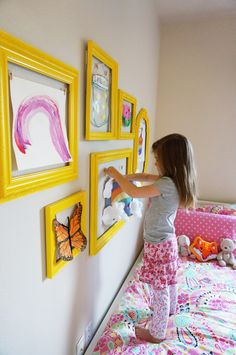 Repurposed picture frames painted bright yellow in children's room or hallway wall gallery, bedroom showcase kids art work by The Caterpillar Years. Upcycle, Recycle, Salvage, diy, thrift, flea, repurpose, refashion! For vintage ideas and goods shop at Estate ReSale & ReDesign, Bonita Springs, FL