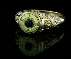 Men's custom designed ring. Hand crafted from a bullet casing and surrounded in hand engraved 14ky gold. Center stone is a sapphire. One of a kind!
