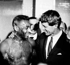 Robert Kennedy embraces Pele at Maracana locker room Brazil, 1965.