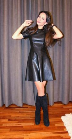 Amateur in flared black leather dress and boots