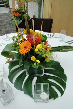 we have those glass squares from Kristy. Add the banana leaf underneath tropical floral centerpieces