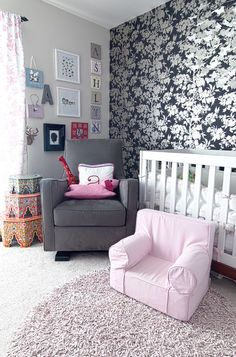 Worldly #baby girl's #nursery with #floral wallpaper, white crib, and pink fluffy #rug.