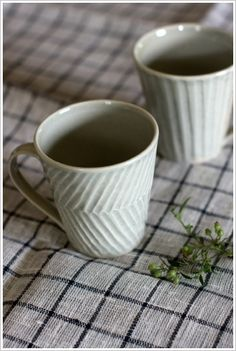 All white mugs with texture.