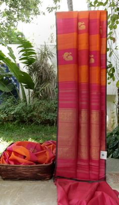 This borderless kanchivaram silk is in magenta, punch pink, tiger orange and ginger orange with gold zari bhuttas. The selvedge is in moss green and seaweed green with the pallu in punch pink intri…