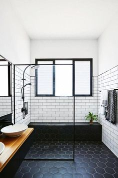 Trend Report: Matte Black – The Evans Edit Kitchen and Bath Industry Show in Orlando, sleek modern bathroom with matte black hexagon floor tile, matte black shower head, matte black shower bench, glass shower wall, white subway tile, wood counter, black cabinetry, white sink basins with matte black faucets #bathroomdiysmallspaces #ModernBathroomShowerBench #whitekitchen