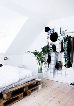 Contemporary, Practical Bedroom Interior with Wire Wall Hangers and Wood Palette Bed