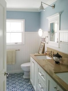 A blue and white color palette brings a calm, coastal feel to this traditional bathroom. White wainscoting protects the sheetrock from daily family use and also adds character to the small space.