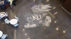 This intricate zinc inlay was polished using the Bomanite Renaissance Custom Polishing System to create a luminous finish that makes this Kansas University Jayhawk the centerpiece of this decorative concrete flooring project. Concrete Overlay, University Of Kansas, Polished Concrete, Art And Technology, Atrium, Concrete Floors, Overlays, Renaissance, Centerpieces